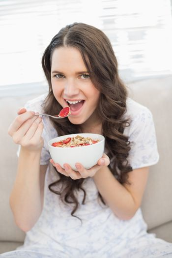 Pretty woman in pyjamas eating fruity cereal