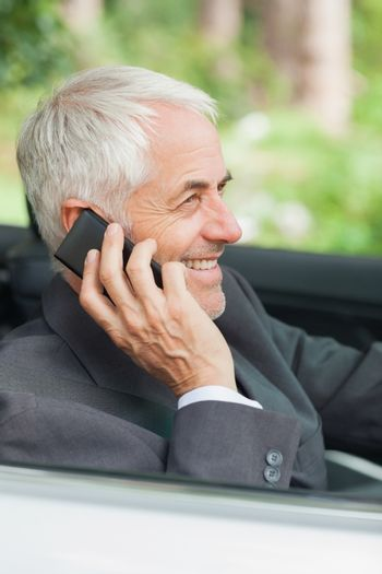 Cheerful mature businessman on the phone driving expensive cabriolet
