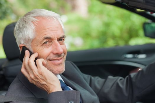 Cheerful businessman on the phone driving expensive cabriolet