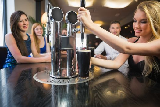 Blonde woman pulling a pint of stout