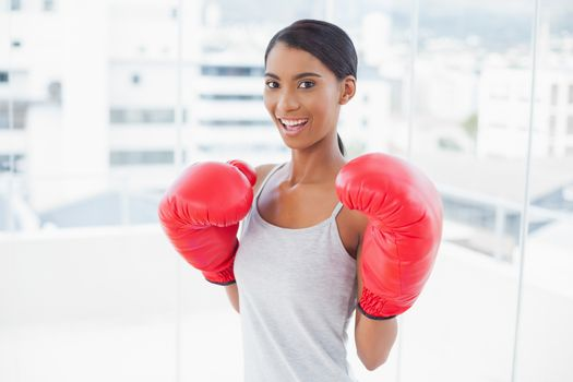 Competitive smiling model wearing red boxing gloves