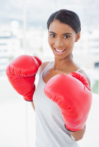 Competitive cheerful model wearing red boxing gloves