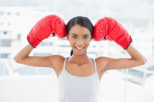 Smiling competitive model wearing red boxing gloves