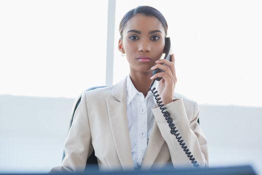 Stern elegant businesswoman on the phone