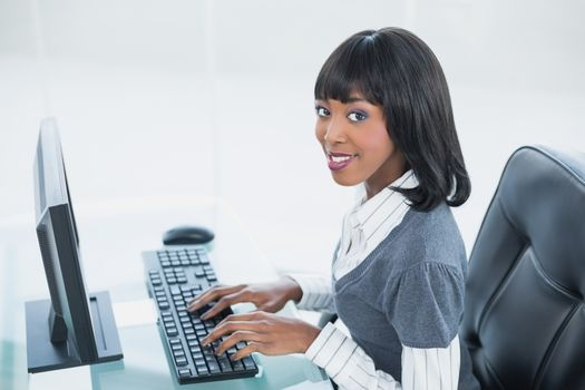 Smiling classy businesswoman typing