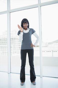 Smiling businesswoman waving