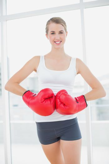 Smiling competitive woman with red boxing gloves posing