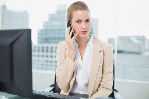 Stern attractive businesswoman on the phone
