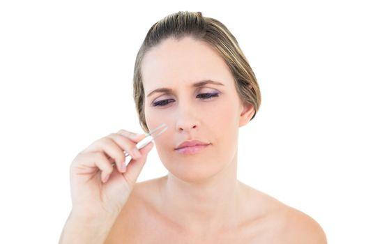 Unsmiling woman looking at her tweezers