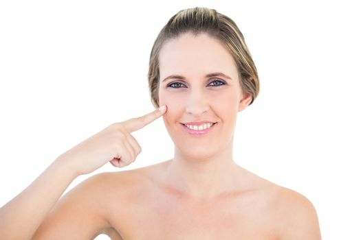 Smiling woman pointing at her cheek
