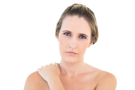 Disgruntled woman looking at camera with a sore shoulder