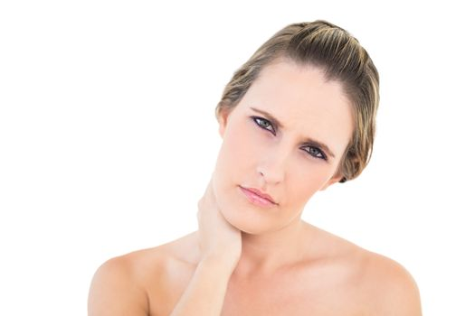 Upset woman looking at camera with a sore neck