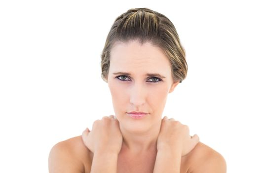 Frowning woman looking at camera with sore shoulders
