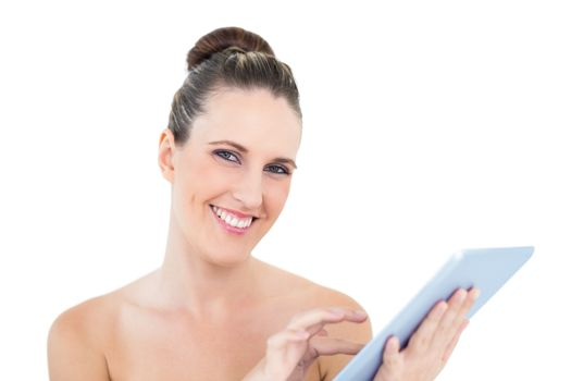 Smiling woman scrolling on her tablet looking at camera