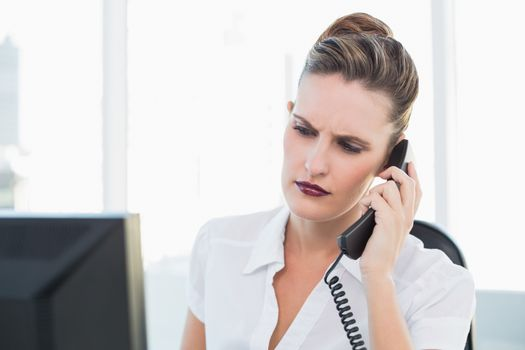 Unsmiling businesswoman talking on the phone