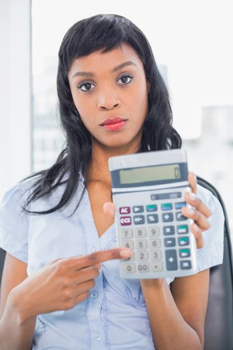 Stern businesswoman holding a calculator