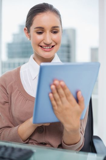 Happy beautiful businesswoman scrolling on her tablet