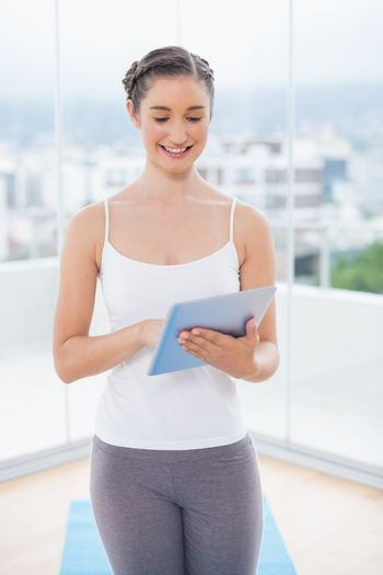 Smiling sporty model scrolling on tablet pc