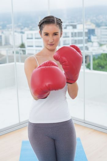 Competitive sporty brunette wearing red boxing gloves