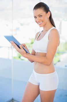 Happy woman wearing sportswear scrolling on tablet