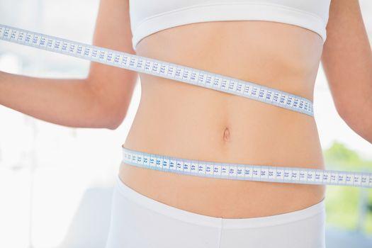 Slender woman measuring her waist during diet