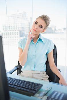 Thoughtful classy businesswoman posing