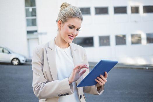 Smiling stylish businesswoman scrolling on digital tablet