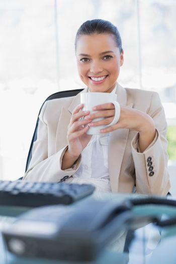 Cheerful sophisticated businesswoman holding coffee