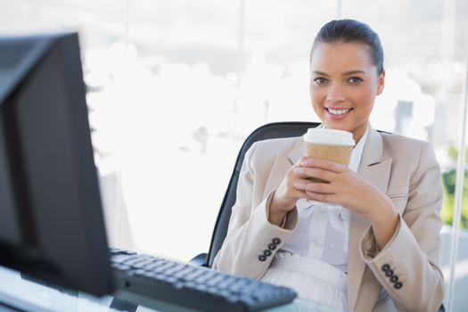 Happy sophisticated businesswoman holding coffee