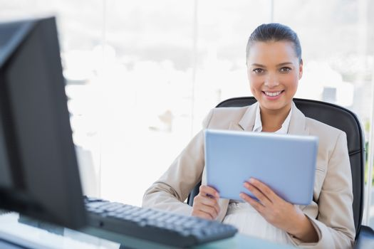 Cheerful sophisticated businesswoman holding tablet pc