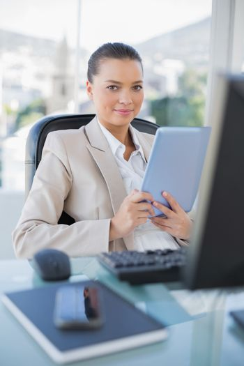 Happy sophisticated businesswoman holding tablet pc