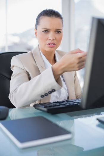 Worried sophisticated businesswoman working on computer