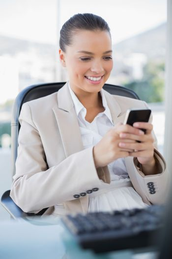 Cheerful sophisticated businesswoman text messaging