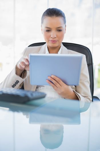 Focused sophisticated businesswoman holding tablet computer