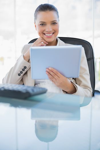 Smiling sophisticated businesswoman holding tablet computer