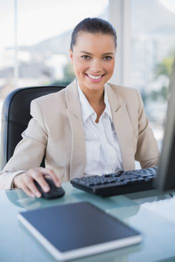 Cheerful sophisticated businesswoman working on computer