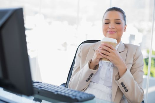 Happy sophisticated businesswoman smelling coffee