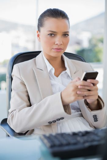 Serious sophisticated businesswoman texting