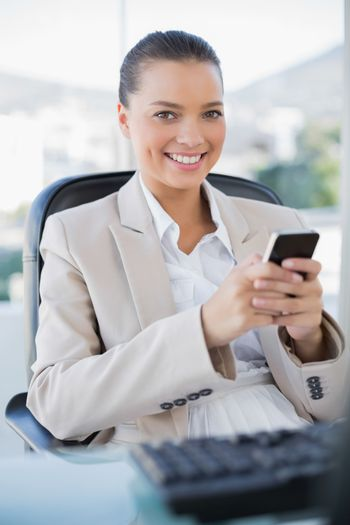 Smiling sophisticated businesswoman text messaging