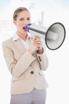 Energetic blonde businesswoman screaming in megaphone