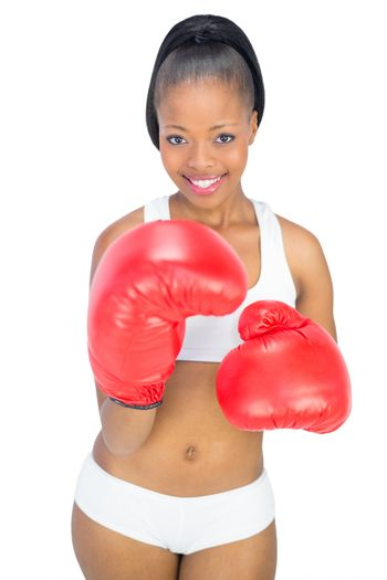 Competitive smiling woman wearing red boxing gloves