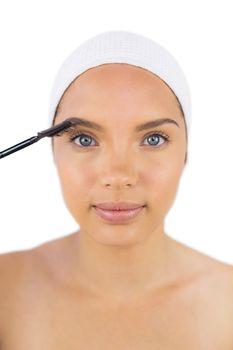 Sensual woman wearing headband using eyebrow brush