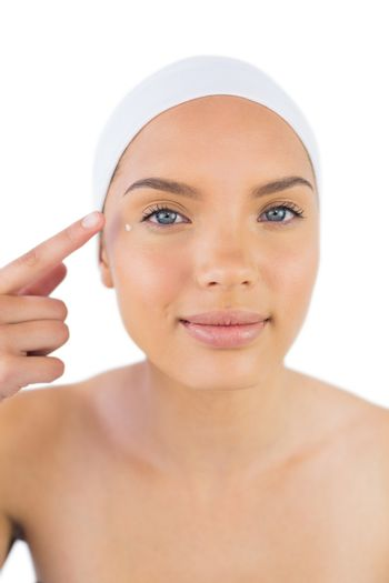 Attractive woman weaing headband putting cream on her face
