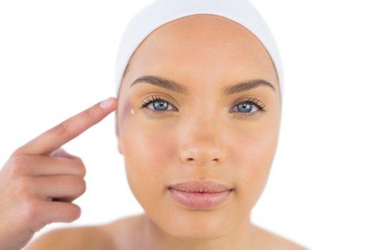 Pretty woman wearing headband putting cream on her face