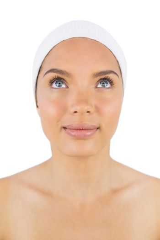 Smiling woman wearing white headband looking upwards