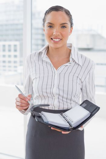 Smiling businesswoman holding her appointment calendar