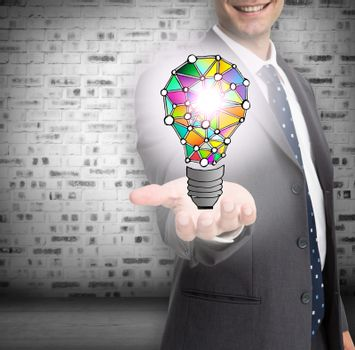 Close up of businessmans hand showing holographic light bulb