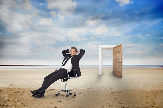 Businessman on swivel chair on the beach