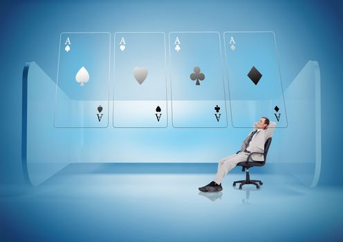 Businessman on swivel chair looking at holographic cards