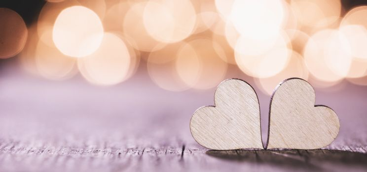 Two handmade wooden hearts on beautiful golden bokeh background. Vintage style. Love Valentine's Day concept.